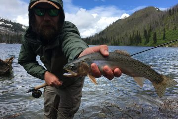 Man holding flyrod and Westslope Black Spotted Cutthroat Trout while standing at a lake shore.